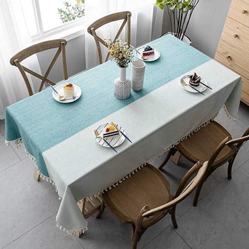 Căn bếp trở nên thoáng mát với ghế ăn gỗ và khăn trải bàn màu xanh